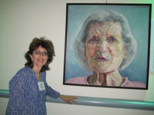 Artist Janet Boltax in front of one of her portraits