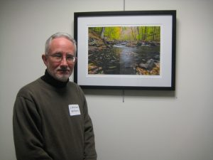 J. Michael Williams in front of his photo  Swirling Leaves